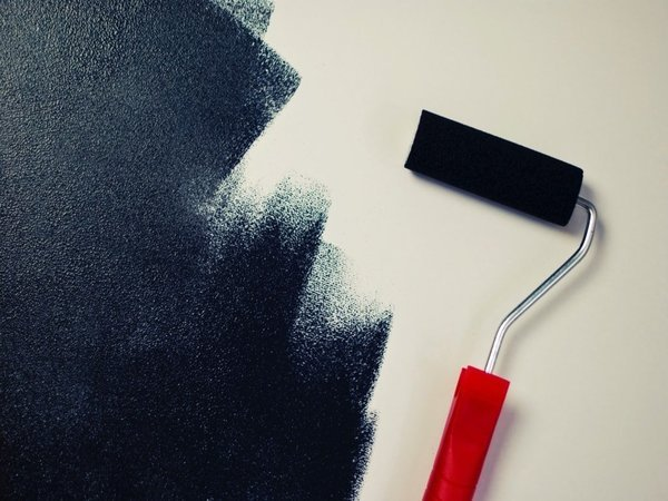 Roller painting a wall