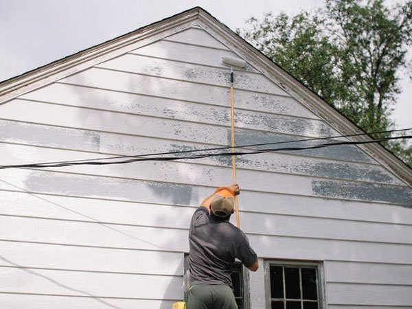 These exterior house painting tips can have you painting a house like this man