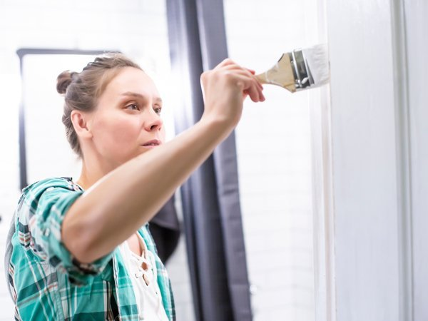 Woman painting her bathroom with a semi-gloss paint sheen